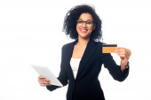African american businesswoman holding digital tablet, smiling and showing credit card isolated on white