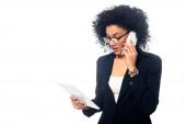 Afroamerikanische Geschäftsfrau hält digitales Tablet in der Hand und telefoniert isoliert auf weißem Grund