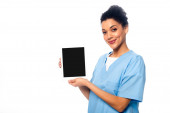 African american nurse looking at camera and showing digital tablet isolated on white