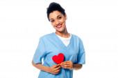 Glückliche und positive afrikanisch-amerikanische Krankenschwester präsentiert dekoratives Herz isoliert auf weiß
