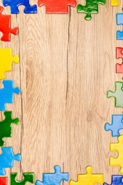 Top view of colorful pieces of puzzle on wooden background, autism concept stock vector