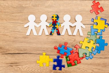 Top view of special kid with autism among another and pieces of bright colorful puzzle on wooden background stock vector