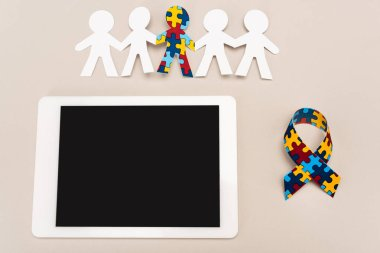 Top view of awareness ribbon, digital tablet and special kid with autism among another on white background stock vector