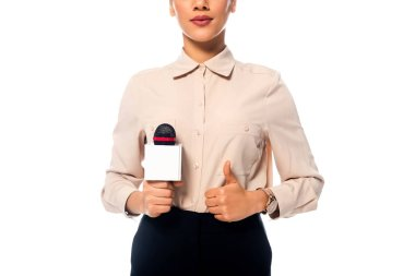 Partial view of african american journalist with thumb up holding microphone isolated on white