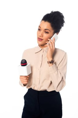 Thoughtful african american journalist with microphone talking on smartphone isolated on white