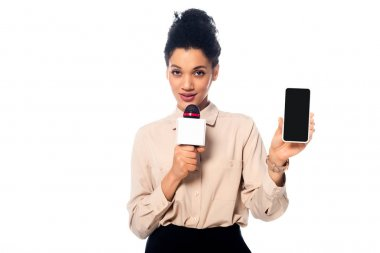 African american journalist speaking into microphone and presenting smartphone isolated on white