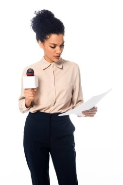 Front view of concentrated african american journalist with microphone reading documents isolated on white