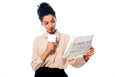 African american journalist speaking into microphone and looking on newspaper with economic news lettering isolated on white