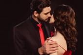 Eleganter Mann küsst Freundin beim Ausziehen Kleid isoliert auf schwarz