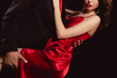 Photo Cropped view of elegant man embracing and holding by led seductive woman in red dress isolated on black