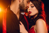 Sensual woman touching chest of handsome boyfriend with unbuttoning shirt on black background with lighting