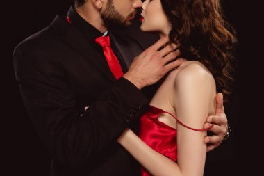 Cropped view of elegant man kissing and taking off red dress from girlfriend isolated on black