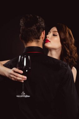 Beautiful woman with glass of wine embracing boyfriend isolated on black stock vector