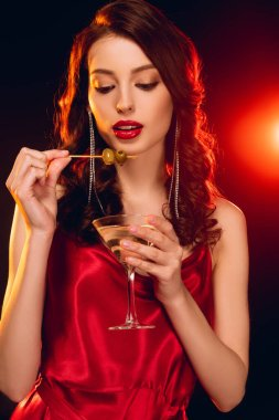 Beautiful woman holding stick with olives and glass of martini on black background with lighting stock vector