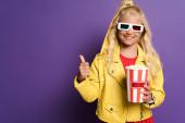 usmívající se dítě s 3D brýle drží vědro s popcornem a ukazuje jako na fialovém pozadí