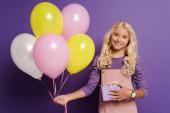 usmívající se dítě drží balónky a dárkové krabice na fialovém pozadí