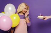 Fotografie oříznutý pohled ženy dávat talíř s narozeninovým dortem na usmívající se dítě s balónky na fialovém pozadí