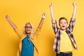 smiling kids showing yes gesture and looking at camera on yellow background