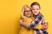 usmívající se děti objímající a dívající se na kameru na žlutém pozadí