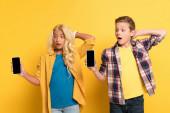 překvapené děti držící smartphony s kopírovacím prostorem na žlutém pozadí