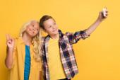 usmívající se dítě ukazující mír gesto a přítel přičemž selfie na žlutém pozadí