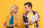 usmívající se dítě při pohledu na digitální tablet svého přítele na žlutém pozadí