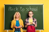 usmívající se školáci s batohy stojící u tabule s nápisem zpět do školy