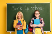 smiling schoolkids holding books and standing near chalkboard with back to school lettering