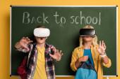 Schockierte Schüler mit Virtual-Reality-Headsets stehen neben Kreidetafel mit Schulbuchstaben