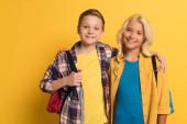 mosolygós iskolás gyerekek hátizsákkal ölelés és nézi kamera sárga háttér