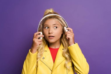excited kid with headphones looking away on purple background