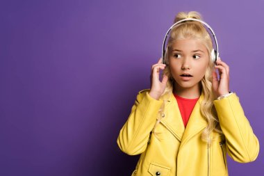 shocked kid with headphones looking away on purple background
