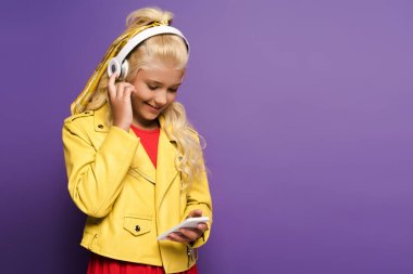 smiling kid with headphones using smartphone on purple background