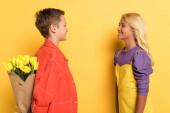 oldal kilátás mosolygós fiú bujkál csokor az ő aranyos barátja sárga háttér