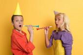 schockierte Kinder mit Party-Mützen mit Party-Hupen auf gelbem Hintergrund