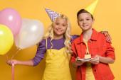 mosolygós gyerekek party sapka tartja léggömbök és lemez születésnapi torta sárga háttér
