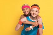 Fotografie usmívající se děti ve sportovním oblečení objímání a pohled na kameru na žlutém pozadí