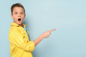 šokované a roztomilé dítě ukazuje prstem na modré pozadí
