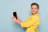 Lächelndes Kind mit digitalem Tablet und Blick auf Kamera auf blauem Hintergrund