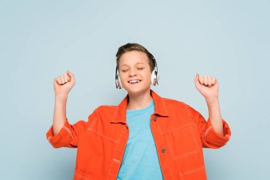 smiling boy with headphones listening to music on blue background