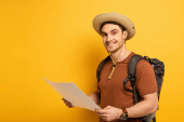 handsome smiling tourist in hat with backpack holding map on yellow
