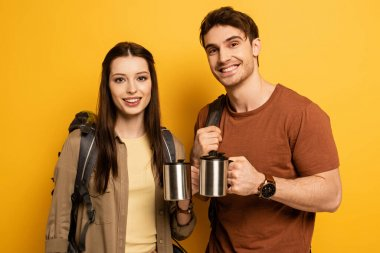 Couple of smiling tourists with backpacks holding cups with coffee on yellow stock vector