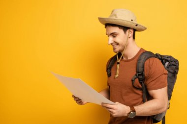 Handsome smiling tourist in hat with backpack looking at map on yellow stock vector