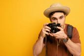 pohledný turista v klobouku s batohem fotografování na kameru na žluté