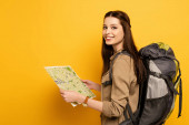 smiling female tourist with backpack holding map on yellow