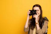 atraktivní žena turista s batohem drží fotoaparát na žluté