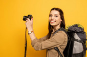 beautiful smiling tourist with backpack holding photo camera on yellow