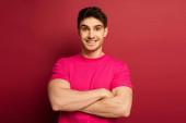 portrét usmívajícího se muže v růžovém tričku se zkříženýma rukama na červené