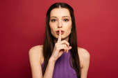 Photo portrait of beautiful woman showing silence symbol on red