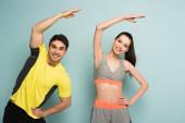 glückliches sportliches Paar, das in Sportkleidung auf blau trainiert